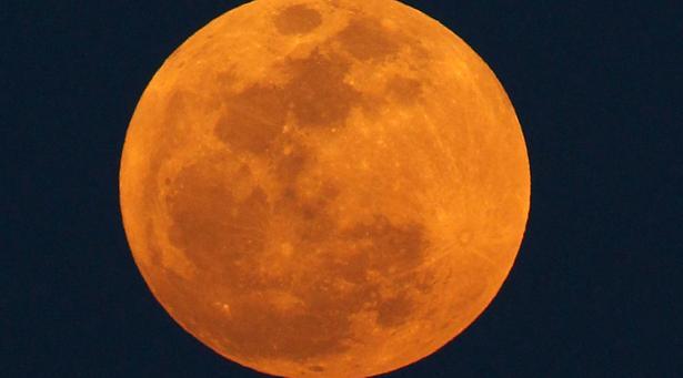 The moon rises in the Atlantic Ocean near Bal Harbour, Fla.