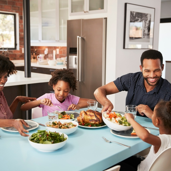 Family enjoying a meal around the table. (Getty Images)