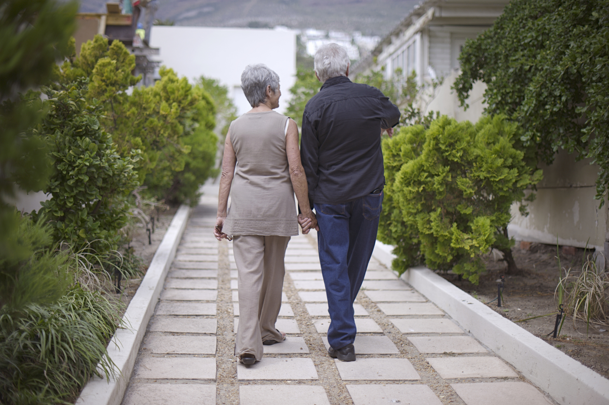 Elderly couple walking in garden. (Getty Images)