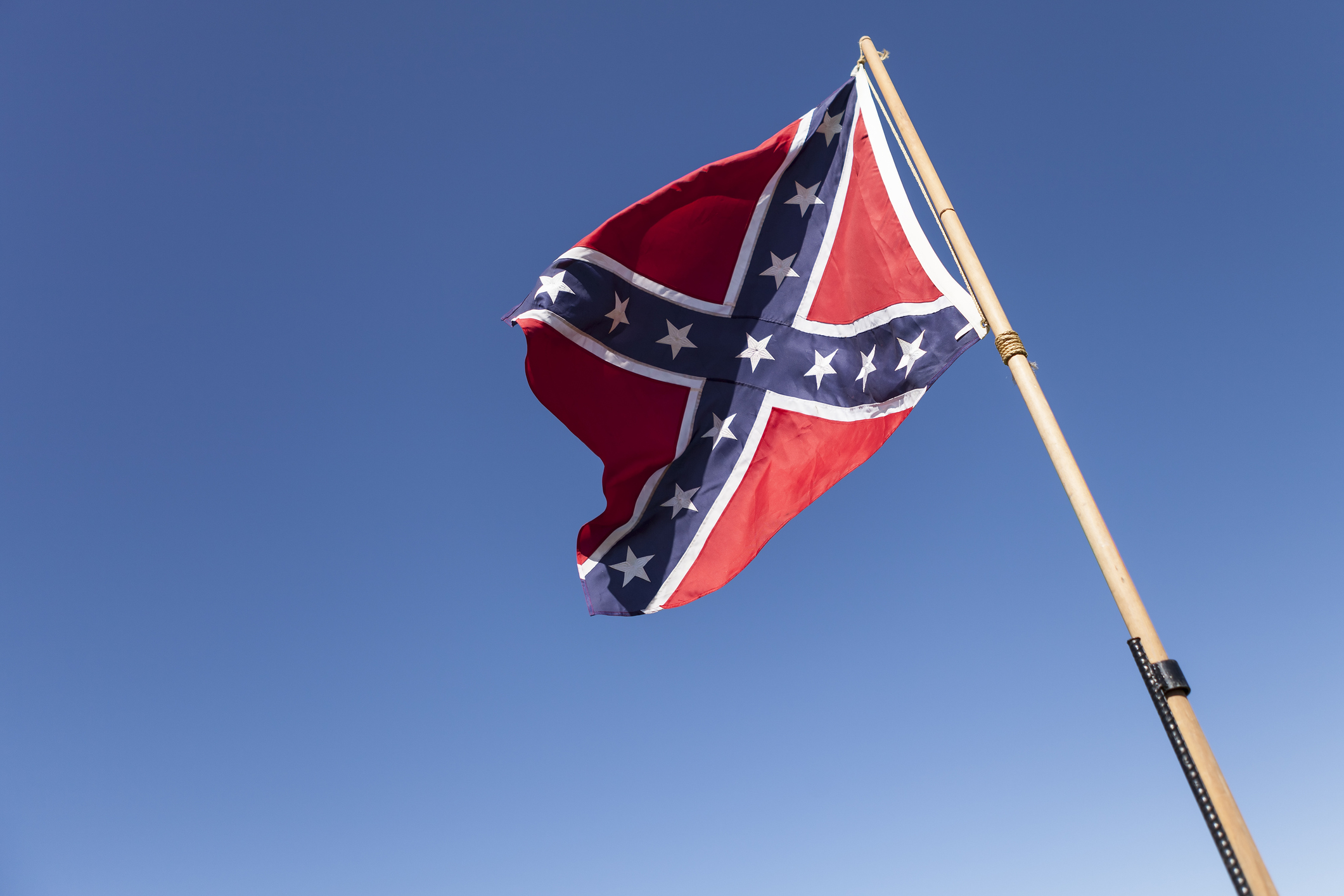 Confederate Flag on pole over blue sky.(Getty Images)