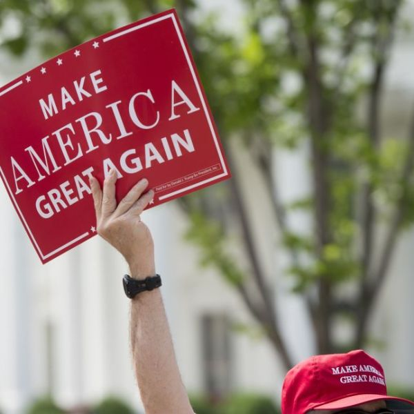 """A man holds a Make America Great Again sign as supporters of US President Donald Trump and his policies demonstrate during a """"Pittsburgh Not Paris"""" rally in support of his decision to withdraw the US from the Paris Climate Accord during a rally in Lafayette Square next to the White House in Washington, DC, on June 3, 2017. (SAUL LOEB/AFP/Getty Images)"""