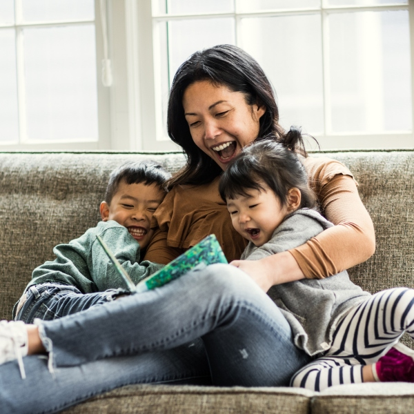 Mother reading to kids on couch (Getty Images)