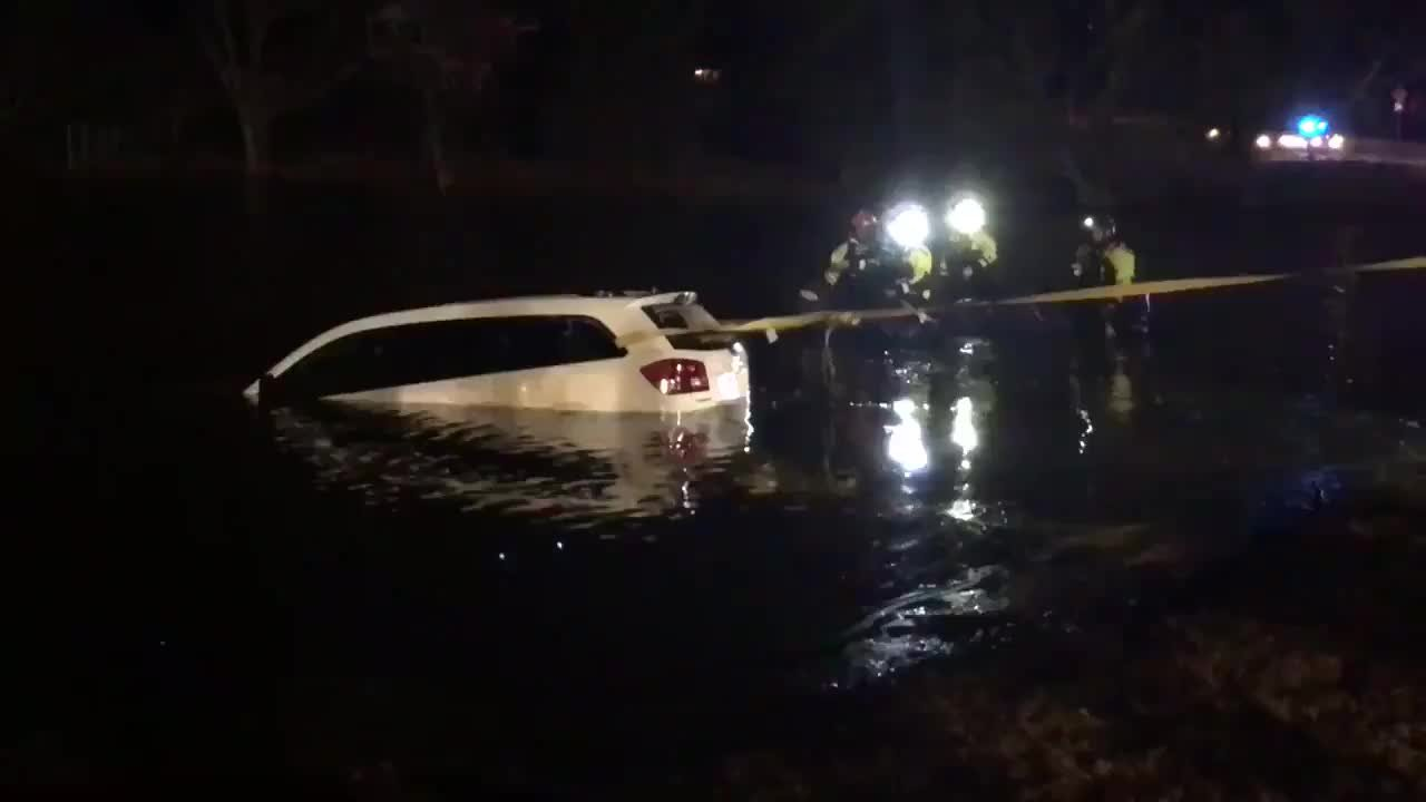 A white Dodge SUV is partially submerged in a lake as fire crews work to pull it out.