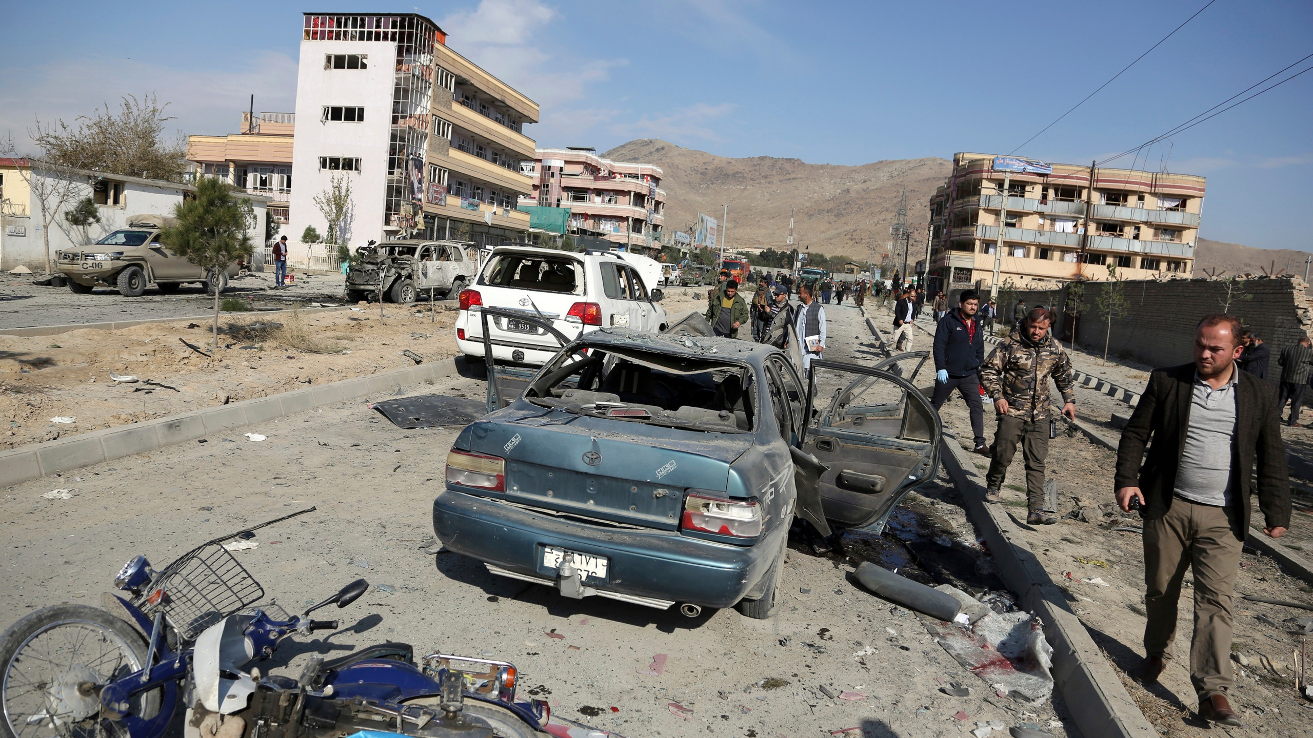 In this Wednesday, Nov. 13, 2019, file photo, Afghan security personnel gather at the site of a car bomb attack in Kabul, Afghanistan. Afghanistan will need vast amounts of foreign funding to keep its government afloat through 2024, a U.S. agency said Thursday, even as foreign donors are increasingly angry over the cost of debilitating corruption and the U.S. seeks a peace deal with Taliban to withdraw its troops. (AP Photo/Rahmat Gul, File)
