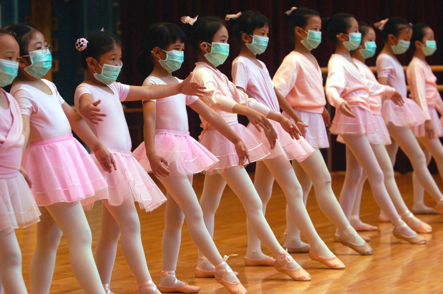 FILE - In this April 27, 2003, file photo, children attend ballet lessons wearing masks to protect themselves from severe acute respiratory syndrome, SARS, in Hong Kong. During the 2002-2003 outbreak of SARS, a related virus, experts discovered that more than 300 people were infected through a defective sewage system in a Hong Kong housing estate. (AP Photo/Vincent Yu, File)