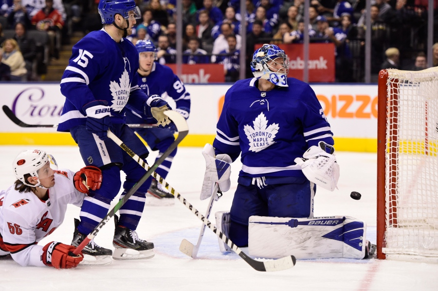 Toronto Maple Leafs goaltender Frederik Andersen (31) looks back at his net after Carolina Hurricanes center Martin Necas (not shown) scored during third-period NHL hockey game action in Toronto, Saturday, Feb. 22, 2020. Hurricanes left wing Erik Haula (56) and Maple Leafs center Alexander Kerfoot (15) look on. (Frank Gunn/The Canadian Press via AP)