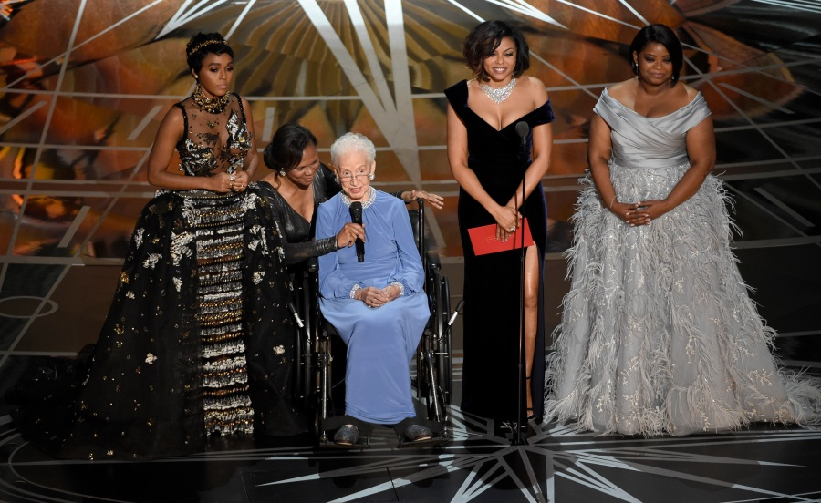 """FILE - In this Feb. 26, 2017, file photo Janelle Monae, left, Taraji P. Henson, second right and Octavia Spencer, right, introduce Katherine Johnson, seated, the inspiration for """"Hidden Figures,"""" as they present the award for best documentary feature at the Oscars at the Dolby Theatre in Los Angeles. Johnson, a mathematician on early space missions who was portrayed in film """"Hidden Figures,"""" about pioneering black female aerospace workers, died Monday, Feb. 24, 2020. (Photo by Chris Pizzello/Invision/AP, File)"""