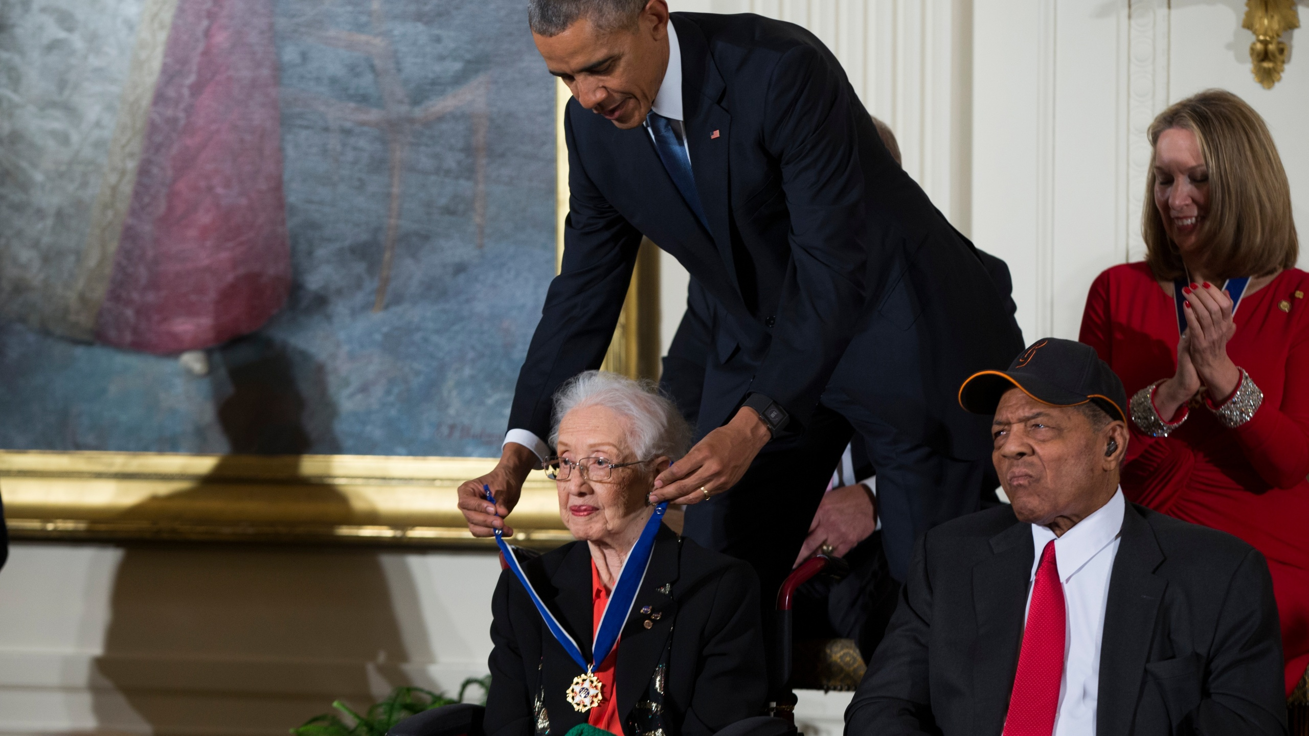 "FILE - In this Nov. 24, 2015 photo, Willie Mays, right, looks on as President Barack Obama presents the Presidential Medal of Freedom to NASA mathematician Katherine Johnson during a ceremony in the East Room of the White House, in Washington. Johnson, a mathematician on early space missions who was portrayed in film ""Hidden Figures,"" about pioneering black female aerospace workers, died Monday, Feb. 24, 2020. (AP Photo/Evan Vucci, File)"