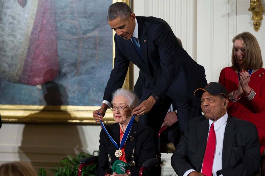 """FILE - In this Nov. 24, 2015 photo, Willie Mays, right, looks on as President Barack Obama presents the Presidential Medal of Freedom to NASA mathematician Katherine Johnson during a ceremony in the East Room of the White House, in Washington. Johnson, a mathematician on early space missions who was portrayed in film """"Hidden Figures,"""" about pioneering black female aerospace workers, died Monday, Feb. 24, 2020. (AP Photo/Evan Vucci, File)"""