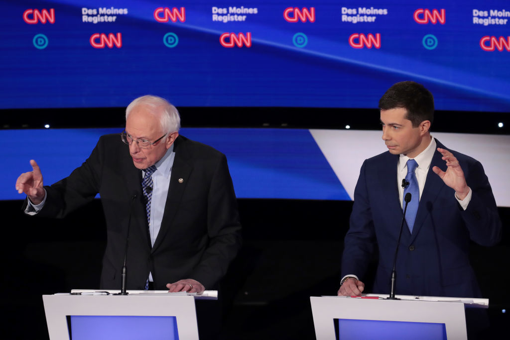 (From right) Former South Bend, Indiana Mayor Pete Buttigieg listens as Sen. Bernie Sanders (I-VT) makes a point during the Democratic presidential primary debate at Drake University on January 14, 2020 in Des Moines, Iowa. (Photo by Scott Olson/Getty Images)
