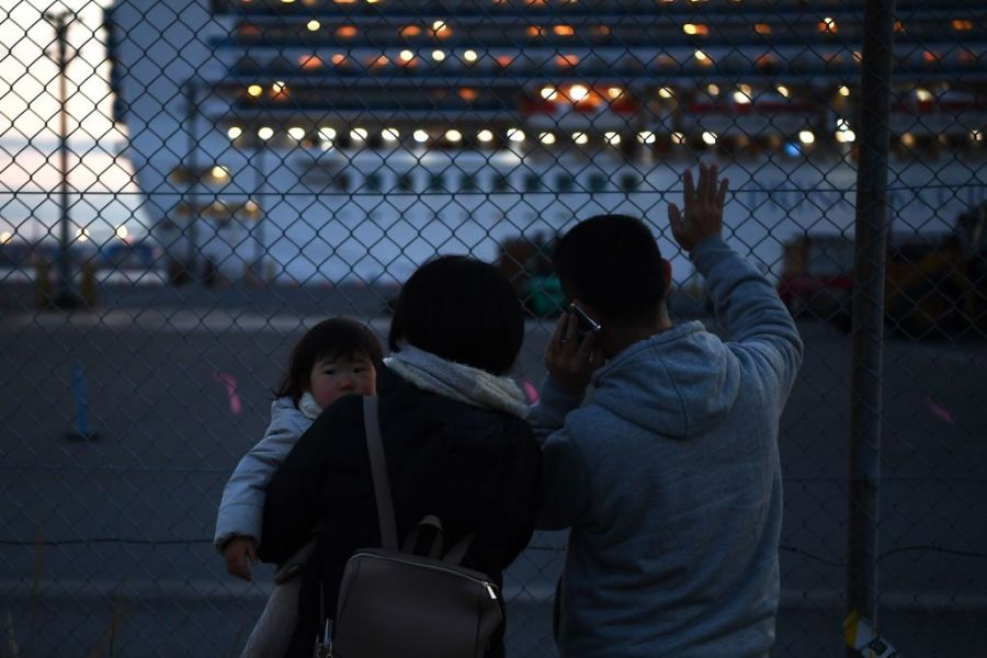 "Relatives of passengers wave towards the Diamond Princess cruise ship, with around 3,600 people quarantined onboard due to fears of the new coronavirus, as the ship departs from Daikoku Pier Cruise Terminal in Yokohama on February 11, 2020, for a day to dump waste water and generate potable water. - The death toll from a new coronavirus outbreak surged past 1,000 on February 11 as the World Health Organization warned infected people who have not travelled to China could be the spark for a ""bigger fire"". (Photo by CHARLY TRIBALLEAU / AFP) (Photo by CHARLY TRIBALLEAU/AFP via Getty Images)"