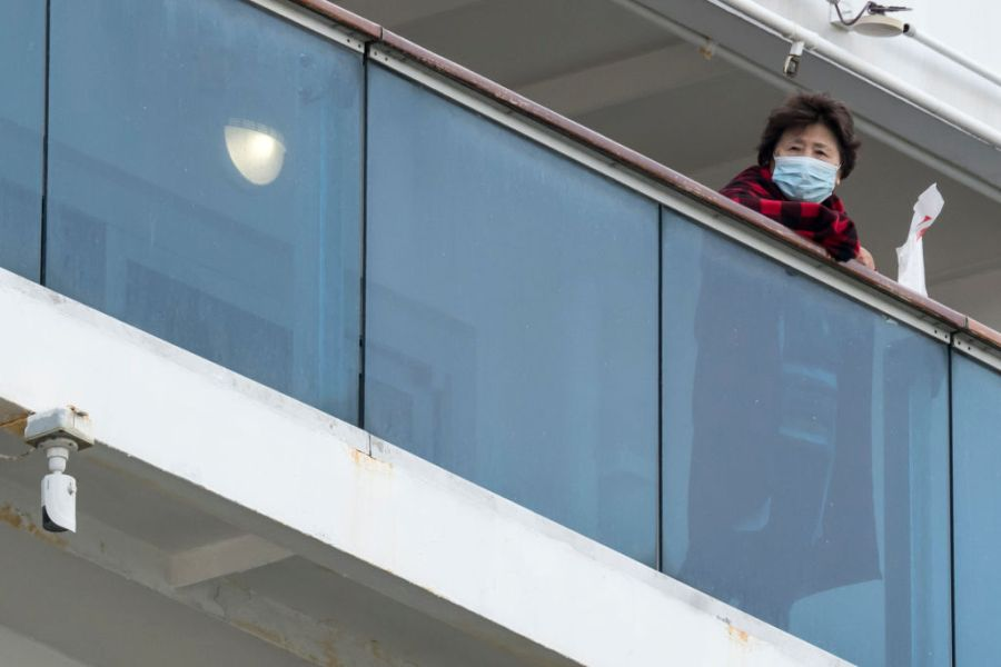 A passenger is seen on a balcony of the Diamond Princess cruise ship as the ship arrives at Daikoku Pier where it is being resupplied and newly diagnosed coronavirus cases taken for treatment as it remains in quarantine after a number of the 3,700 people on board were diagnosed with coronavirus, on February 12, 2020 in Yokohama, Japan. (Photo by Tomohiro Ohsumi/Getty Images)
