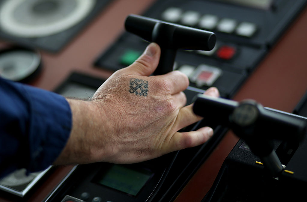 A tattoo is seen on the hand of U.S. Coast Guard senior chief petty officer Louis Coleman as he pilots the U.S. Coast Guard Cutter Hawksbill while on patrol in the Pacific Ocean off of the coast of San Francisco on March 7, 2013. (Photo by Justin Sullivan/Getty Images)