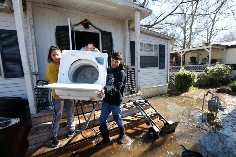 Mario Vargas, right, his sister Alondra Rodriguez, left, and their aunt Nadia Castillo, back, carry a washing machine from Vargas' mother's mobile home in the Harbor Pines Mobile Home Community of Ridgeland, Miss., Friday, Feb. 14, 2020. Officials estimate the flooding along the Pearl River to create the worst flooding in the Capitol city of Jackson and some neighboring communities since 1983. (AP Photo/Rogelio V. Solis)