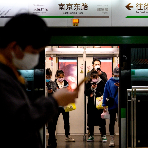 People wearing protective facemasks use their mobile phones on the subway in Shanghai on February 25, 2020. - The new coronavirus has peaked in China but could still grow into a pandemic, the World Health Organization warned, as infections mushroom in other countries. (Photo by NOEL CELIS / AFP) (Photo by NOEL CELIS/AFP via Getty Images)