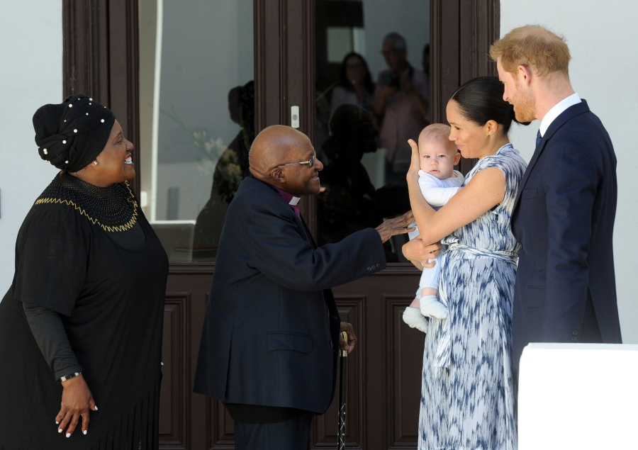 FILE - In this Wednesday, Sept. 25, 2019 file photo, Britain's Prince Harry and Meghan, Duchess of Sussex, holding their son Archie, meet Anglican Archbishop Emeritus, Desmond Tutu and his wife Leah in Cape Town, South Africa. Prince Harry and his wife, Meghan, are fulfilling their last royal commitment Monday March 9, 2020 when they appear at the annual Commonwealth Service at Westminster Abbey. It is the last time they will be seen at work with the entire Windsor clan before they fly off into self-imposed exile in North America. (Henk Kruger/Pool via AP, File)
