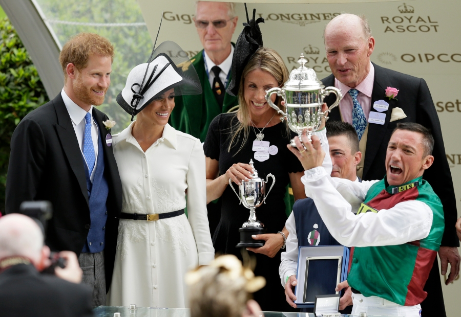 FILE - In this Tuesday, June 19, 2018 file photo, Britain's Prince Harry and Meghan, Duchess of Sussex present the trophy for the St James's Palace Stakes to Frankie Dettori, right, on the first day of the Royal Ascot horse race meeting in Ascot, England. Prince Harry and his wife, Meghan, are fulfilling their last royal commitment Monday March 9, 2020 when they appear at the annual Commonwealth Service at Westminster Abbey. It is the last time they will be seen at work with the entire Windsor clan before they fly off into self-imposed exile in North America. (AP Photo/Tim Ireland, file)