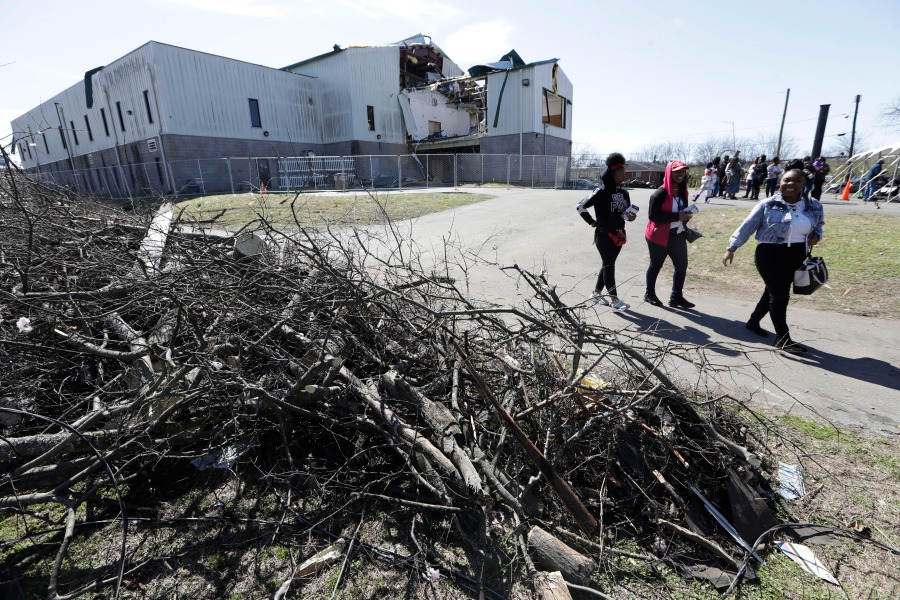 People walk by rubble as they leave a worship service at Mount Bethel Missionary Baptist Church, Sunday, March 8, 2020, in Nashville, Tenn. The congregation held their Sunday service in a tent in the parking lot near the church facilities, which were heavily damaged by a tornado March 3. (AP Photo/Mark Humphrey)