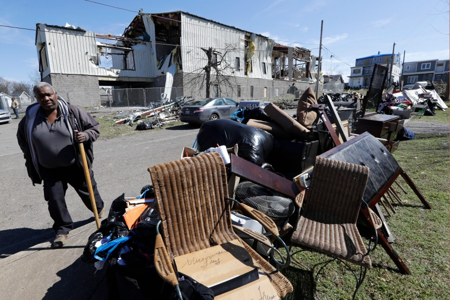 Gene Hancock views damaged goods piled near the street as he leaves a worship service at Mount Bethel Missionary Baptist Church, Sunday, March 8, 2020, in Nashville, Tenn. The congregation held their service in a tent in the parking lot near the church facilities, which were heavily damaged by a tornado March 3. (AP Photo/Mark Humphrey)