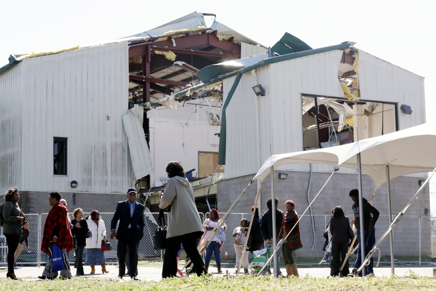People leave a worship service at Mount Bethel Missionary Baptist Church, Sunday, March 8, 2020, in Nashville, Tenn. The congregation held their service in a tent in the parking lot near the church facilities, which were heavily damaged by a tornado March 3. (AP Photo/Mark Humphrey)