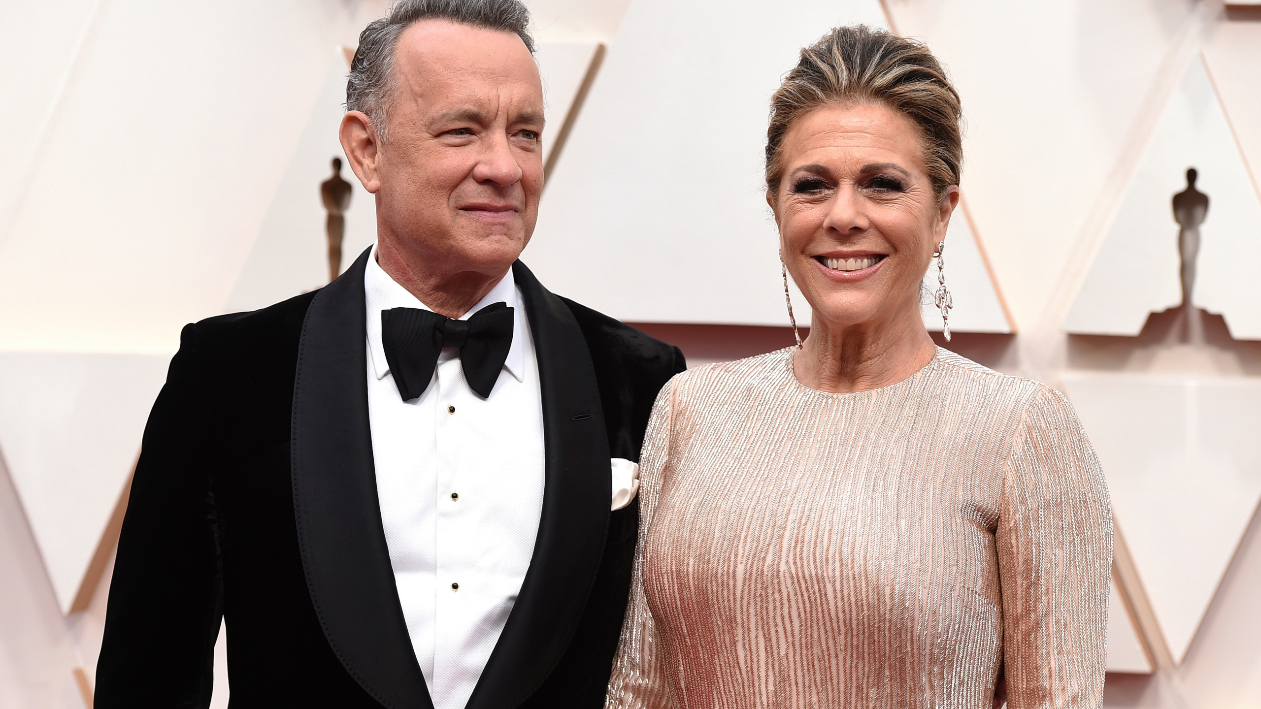 "In this Feb. 9, 2020 file photo, Tom Hanks, left, and Rita Wilson arrive at the Oscars at the Dolby Theatre in Los Angeles. The couple have tested positive for the coronavirus, the actor said in a statement Wednesday, March 11. The 63-year-old actor said they will be ""tested, observed and isolated for as long as public health and safety requires."" (Photo by Jordan Strauss/Invision/AP, File)"