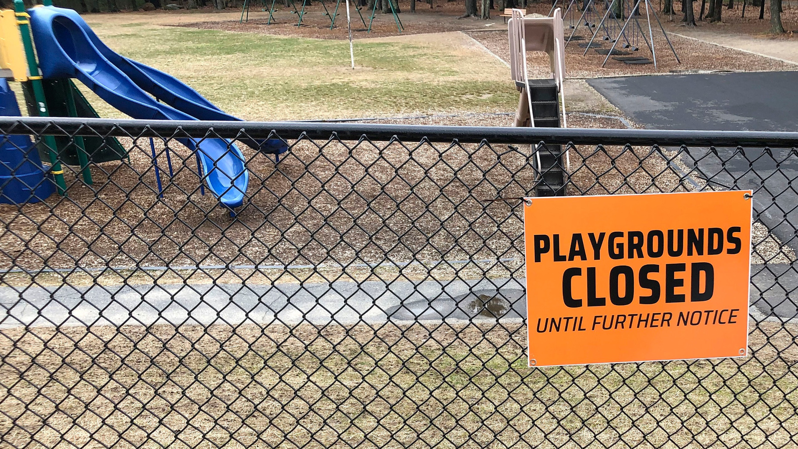 This Friday, March 20, 2020 file photo shows a closed sign near an entrance to a playground at an elementary school in Walpole, Mass., amid the COVID-19 coronavirus outbreak. Child welfare agencies in the U.S. have a difficult mission in the best of times, and now they're scrambling to confront new challenges during the coronavirus outbreak. (AP Photo/Steven Senne)