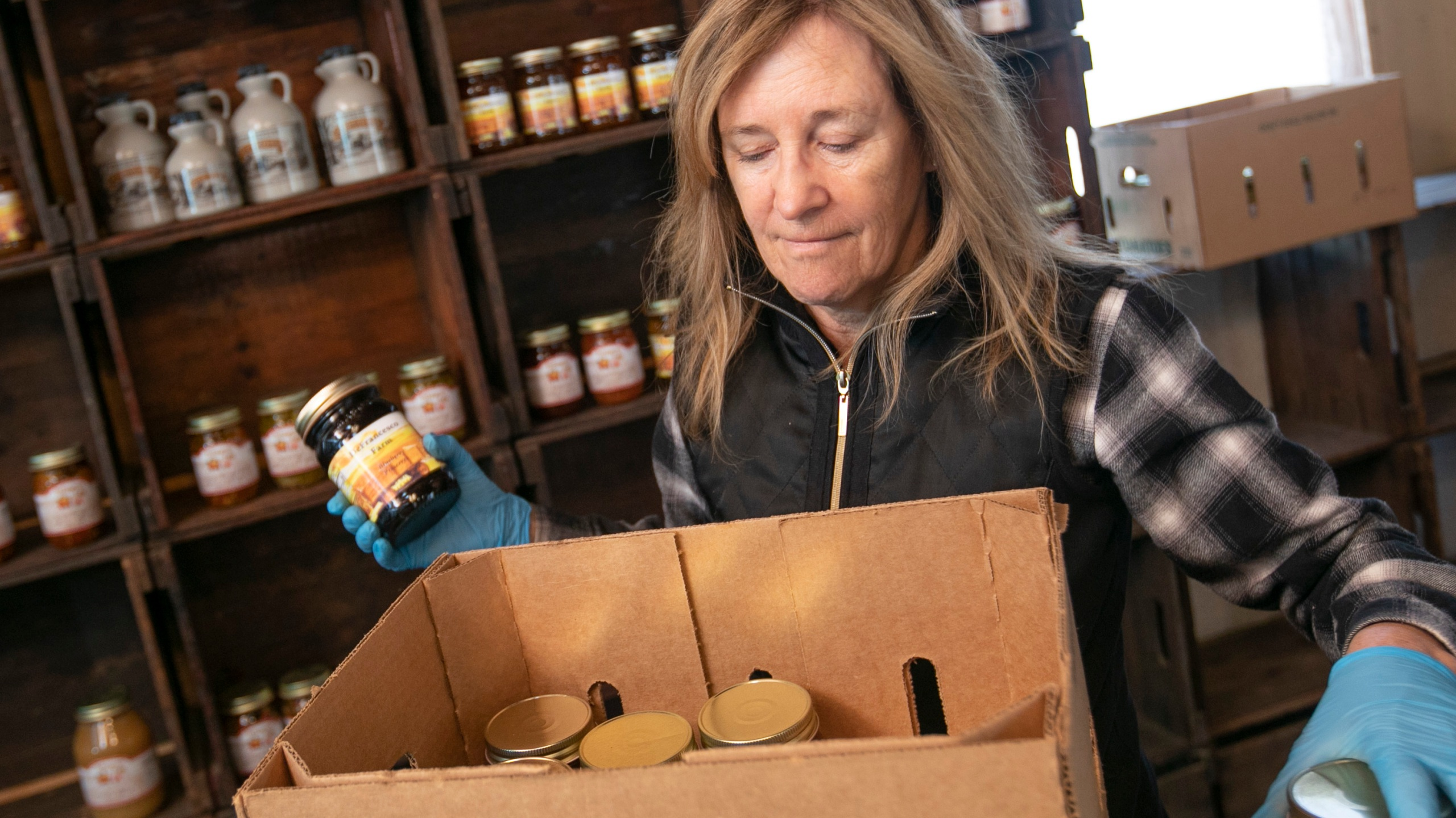 "Linda DeFrancesco stocks shelves with her farm's own salsa, spreads, veggies and salsa at DeFrancesco Farm Stand in Northford, Conn., Thursday, March 26, 2020. Businesses across the state are worried about the impact of the coronavirus, even the ones considered ""essential"" like farmers' markets and garden centers. The farm stand opens Saturday at 10 a.m. (Dave Zajac/Record-Journal via AP)"
