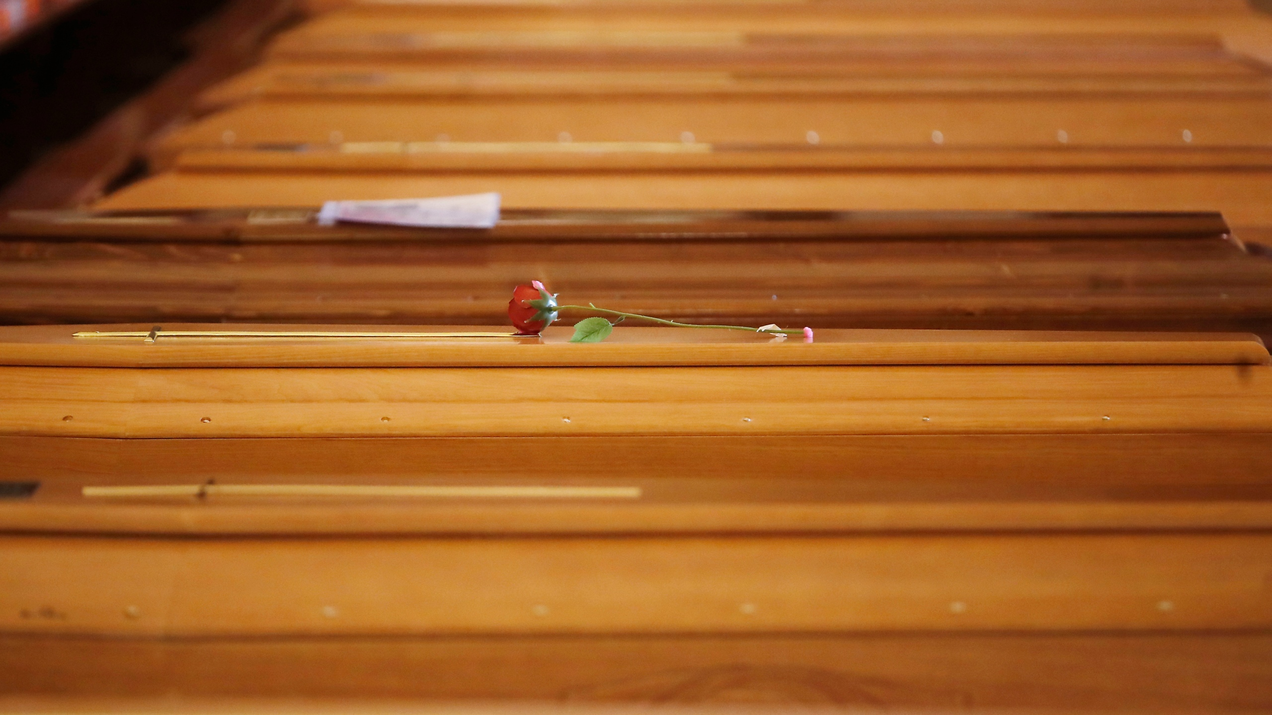 A red rose lies on a coffin lined up along others inside the San Giuseppe church in Seriate, Italy, to be blessed before being sent to crematoriums in Udine and Venice, Northern Italy, Saturday, March 28, 2020. The new coronavirus causes mild or moderate symptoms for most people, but for some, especially older adults and people with existing health problems, it can cause more severe illness or death. (AP Photo/Antonio Calanni)