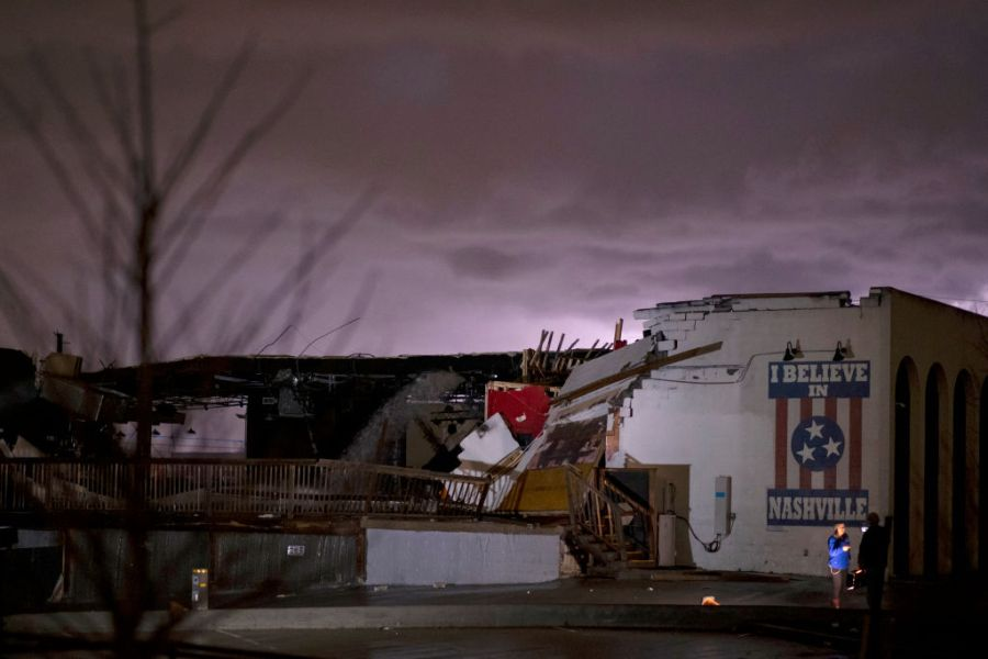 NASHVILLE, TN - MARCH 03:  A television news crew works in front of a mural on heavily damaged The Basement East in the East Nashville neighborhood as lightning strikes in the background on March 3, 2020 in Nashville, Tennessee. (Photo by Brett Carlsen/Getty Images)