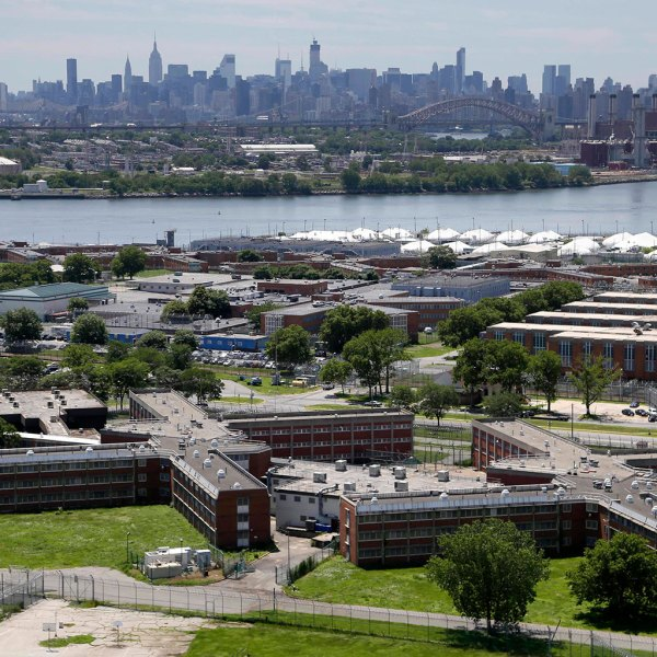 The Rikers Island jail complex stands in New York with the Manhattan skyline in the background. New York City says its jail population is below 9,000 for the first time since 1982, and officials are hailing the drop as a step toward closing the notorious Rikers Island jail complex. Mayor Bill de Blasio said Wednesday, Dec. 27, 2017, the city is on track for a daily average jail population in December of about 8,980 people. (AP Photo/Seth Wenig, File)