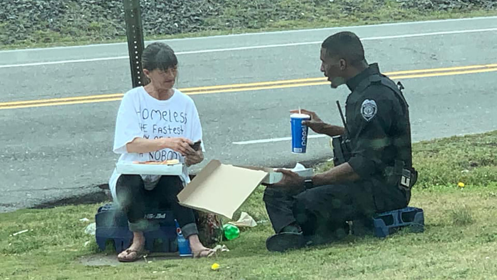 A North Carolina police officer spent his lunch break sharing pizza with a homeless woman and it was captured in a heartwarming photo (Photo: Chris Barnes)