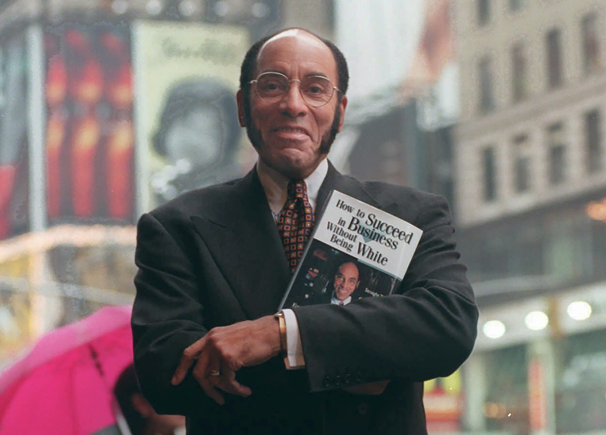 """This Aug. 17, 1997 file photo shows Earl G. Graves Sr. with his book """"How To Succeed In Business Without Being White"""" in New York. Graves Sr., who championed black businesses as the founder of the first African American-owned magazine focusing on black entrepreneurs, has died. He was 85. His son said Graves died Monday, April 6, 2020. (AP Photo/Bebeto Matthews, File)"""