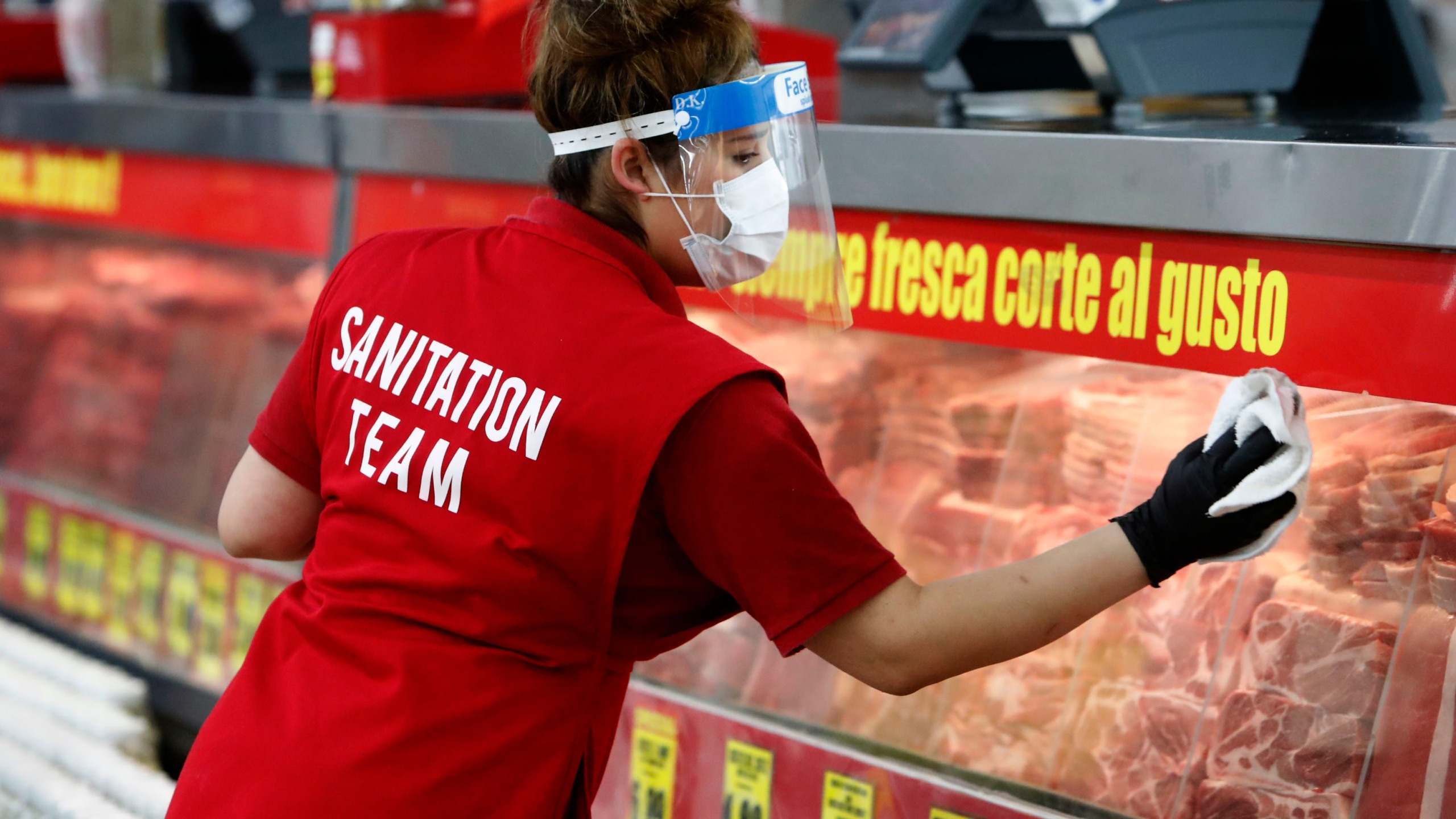 Amid concerns of the spread of COVID-19, Belia Alvarado wipes the meat counter display at El Rancho grocery store in Dallas, Monday, April 13, 2020. (AP Photo/LM Otero)