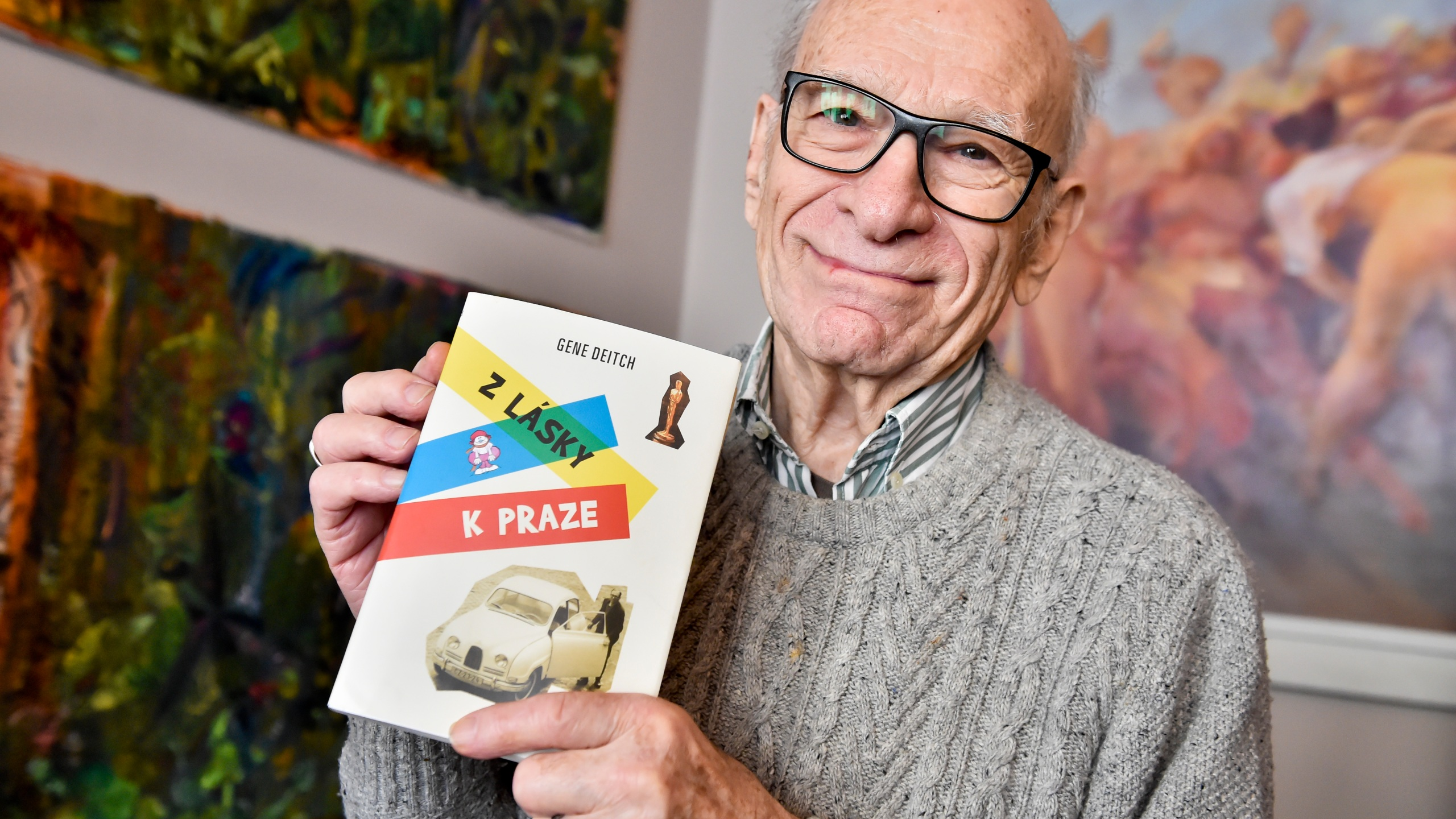FILE - In this February 20, 2018 file photo the American director and animated film producer Gene Deitch poses for the photographer with his book of memories 'For the Love of Prague' in Prague, Czech Republic. Deitch, living in Prague with his Czech wife, animator and producer Zdenka Najmanova, has died at the age of 95 years. Deitch directed Czechoslovak-American animated film 'Munro' that won an Oscar for the Best Animated Short Film in 1961. (Vit Simanek/CTK via AP)