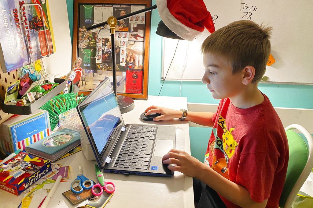 This April 9, 2020, photo released by Kara Illig shows her son, Eli Illig, 10, on his computer in Ebensburg, Pa. (Kara Illig via AP)