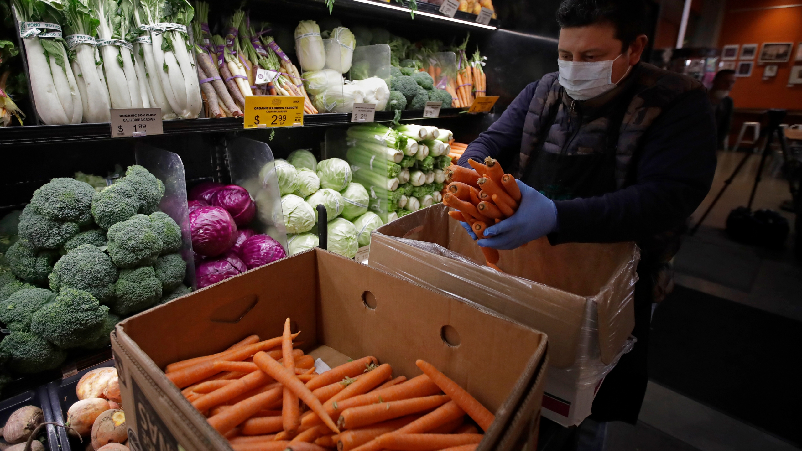 A worker, wearing a protective mask against the coronavirus, stocks produce before the opening of Gus's Community Market, Friday, March 27, 2020, in San Francisco. (AP Photo/Ben Margot)