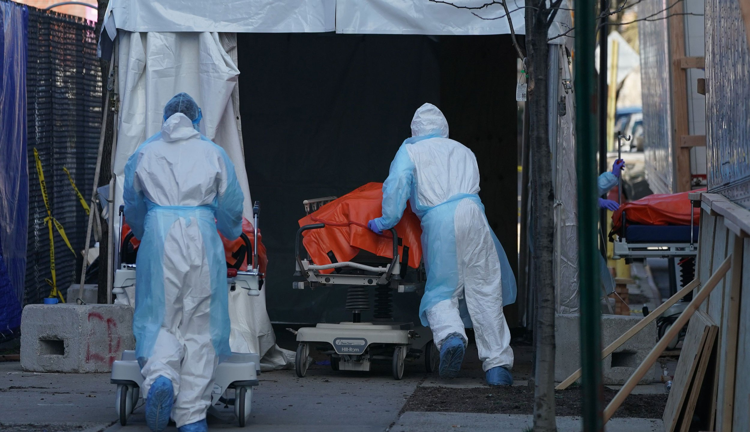 Bodies are moved to a refrigerator truck serving as a temporary morgue outside of Wyckoff Hospital in the Borough of Brooklyn on April 4, 2020 in New York. - New York state's coronavirus toll rose at a devastating pace to 3,565 deaths Saturday, the governor said, up from 2,935 the previous day, the largest 24-hour jump recorded there. (Photo by Bryan R. Smith / AFP)