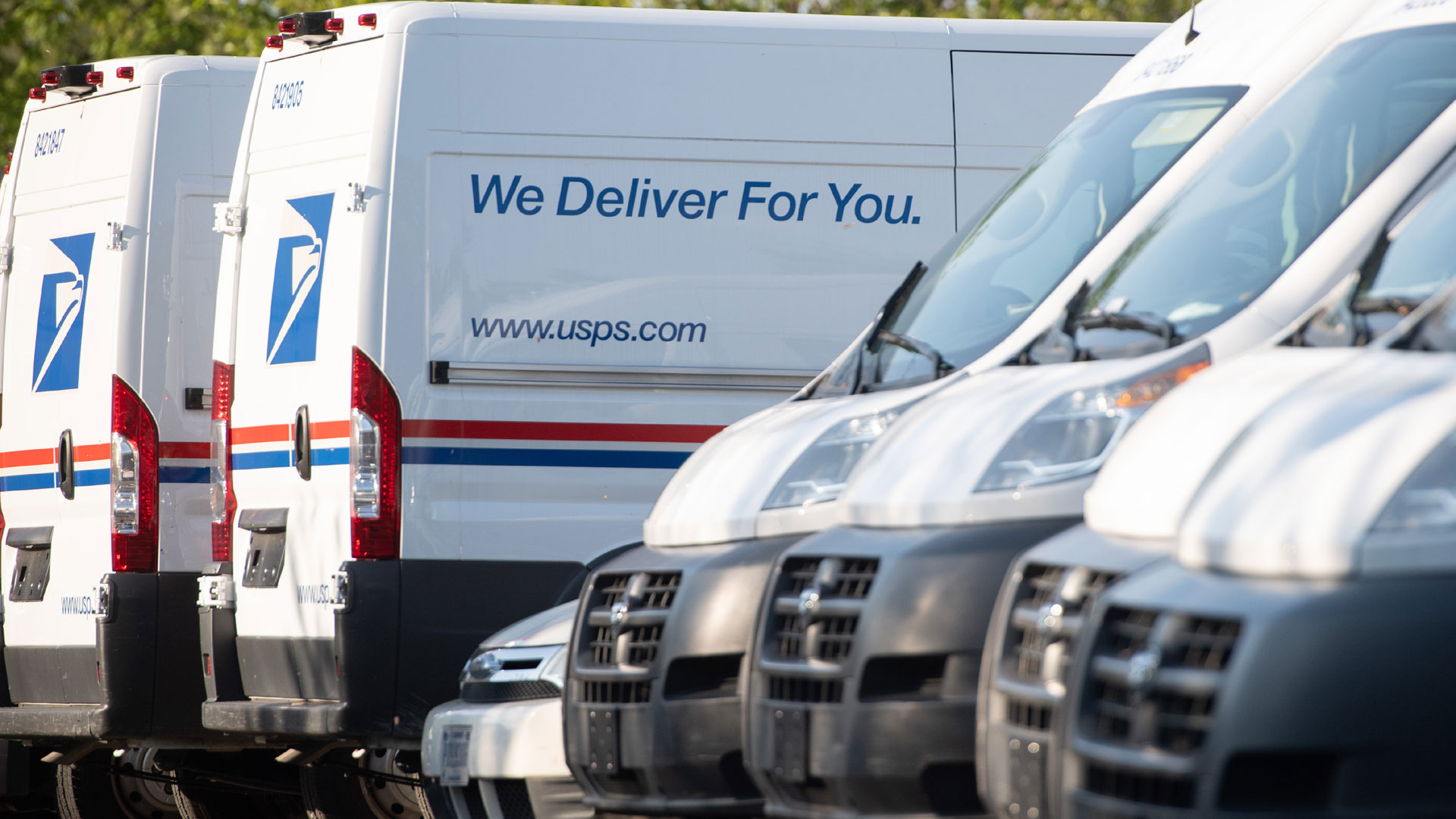 Postal trucks are parked at a United States Postal Service (USPS) post office location. (Photo by SAUL LOEB/AFP via Getty Images)
