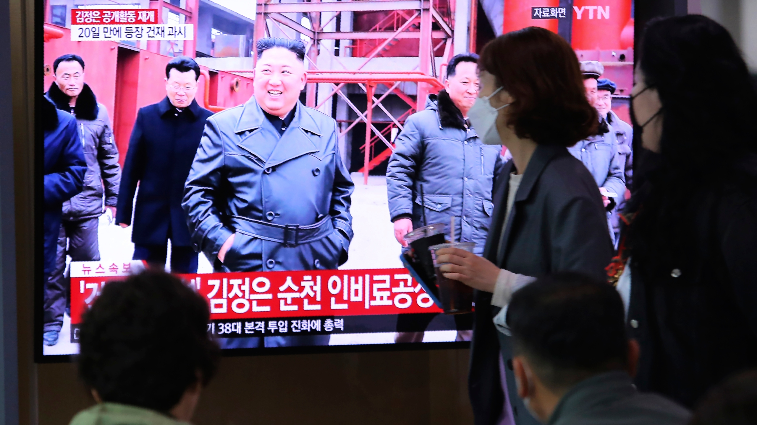 """People watch a TV showing a file image of North Korean leader Kim Jong Un during a news program at the Seoul Railway Station in Seoul, South Korea, Saturday, May 2, 2020. Kim made his first public appearance in several weeks as he celebrated the completion of a fertilizer factory near Pyongyang, state media said Saturday, ending an absence that had triggered global rumors that he was seriously ill. The sign reads: """"Kim Jong Un attended a ceremony marking the completion of a fertilizer factory."""" (AP Photo/Ahn Young-joon)"""