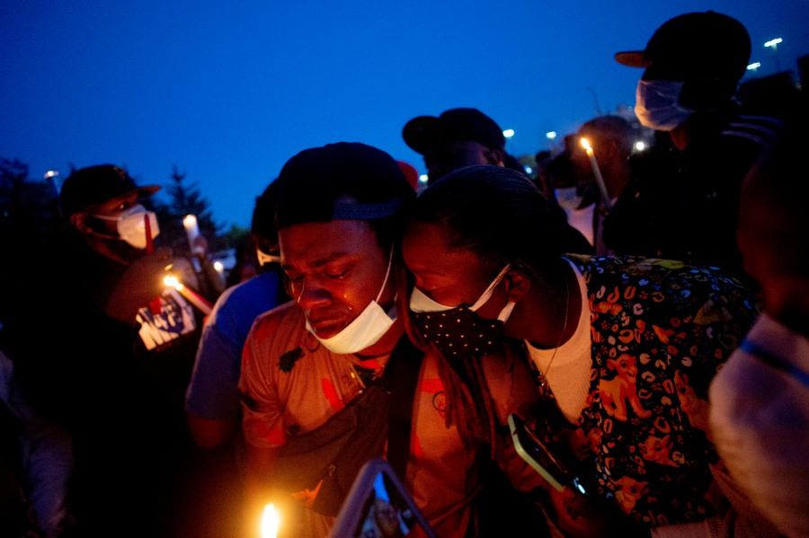 Maalik Mitchell, center left, sheds tears as he says goodbye to his father, Calvin Munerlyn, during a vigil Sunday, May 3, 2020, in Flint, Mich. Munerlyn was shot and killed Friday at a Family Dollar store in Flint. He'd worked at the store as a security guard for a little more than one year. (Jake May/The Flint Journal via AP)