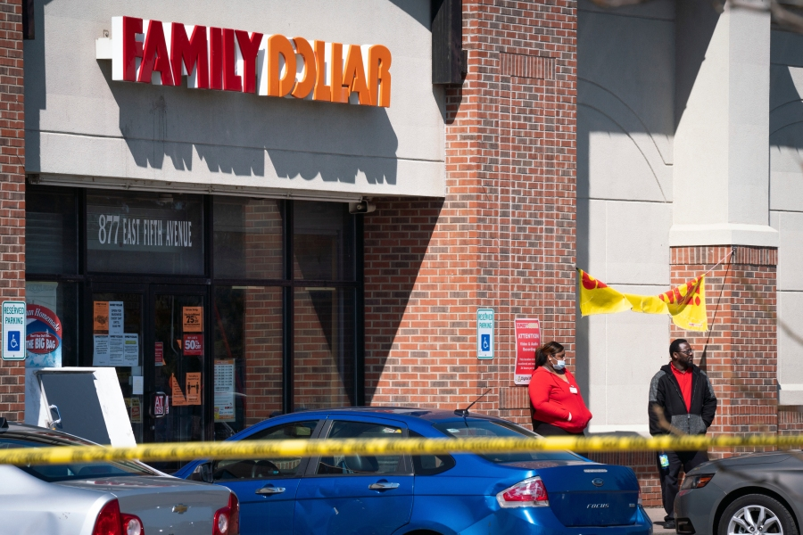 In this Friday, May 1, 2020 photo, employees stand outside the Family Dollar as police investigate a shooting that took place at the store in Flint, Mich. (Sarahbeth Maney/The Flint Journal via AP)