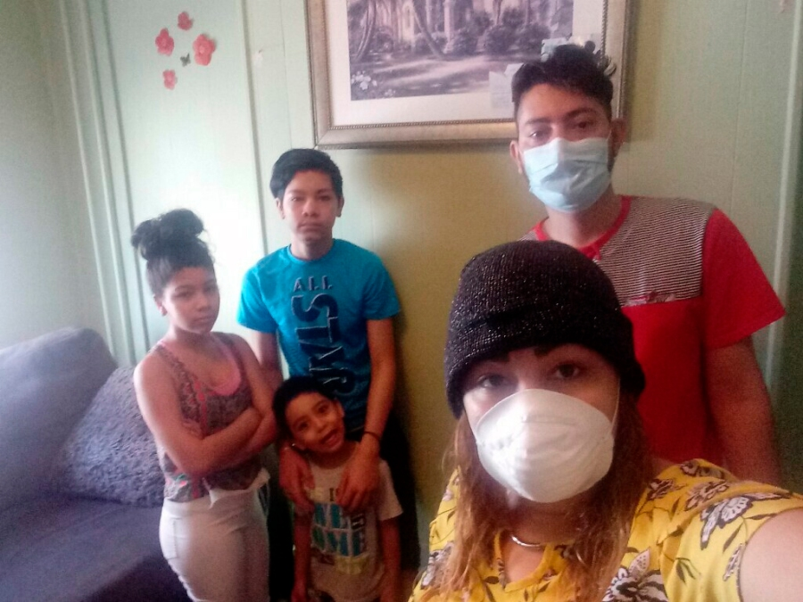 Arely and her husband Rosali, right, take a family photograph with their children Dora, 11, Roberto, 5, and Sirus, 14, after Arely returned from the hospital diagnosed with COVID-19, Thursday May 14 2020, in Baltimore. Having stayed only in her home for months she has no idea how she contracted the virus. (Arely via AP)