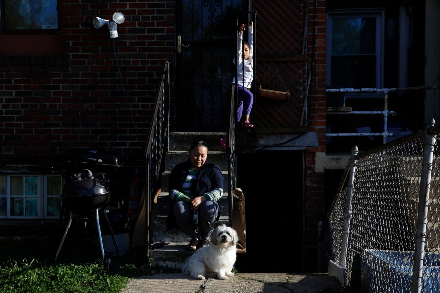 Allison, 5, plays, as her mother Janeth sits outside their basement apartment unit with the family dog, Henry, Wednesday, April 15, 2020, in Washington. Since this image was taken Janeth and her husband Roberto have been diagnosed with COVID-19. (AP Photo/Jacquelyn Martin)