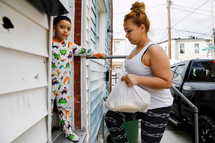 Roberto, 5, stands in their doorway in his pajama's as his mother Arely carries in a bag of food brought to their rental in Baltimore by her sister Janeth, Tuesday, April 14, 2020. Since this image was taken Arely, Janeth, and Janeth's husband Roberto have all been diagnosed with COVID-19, leaving them unable to leave their homes to look for food. Arely was briefly hospitalized with breathing problems as a result of her illness. (AP Photo/Jacquelyn Martin)