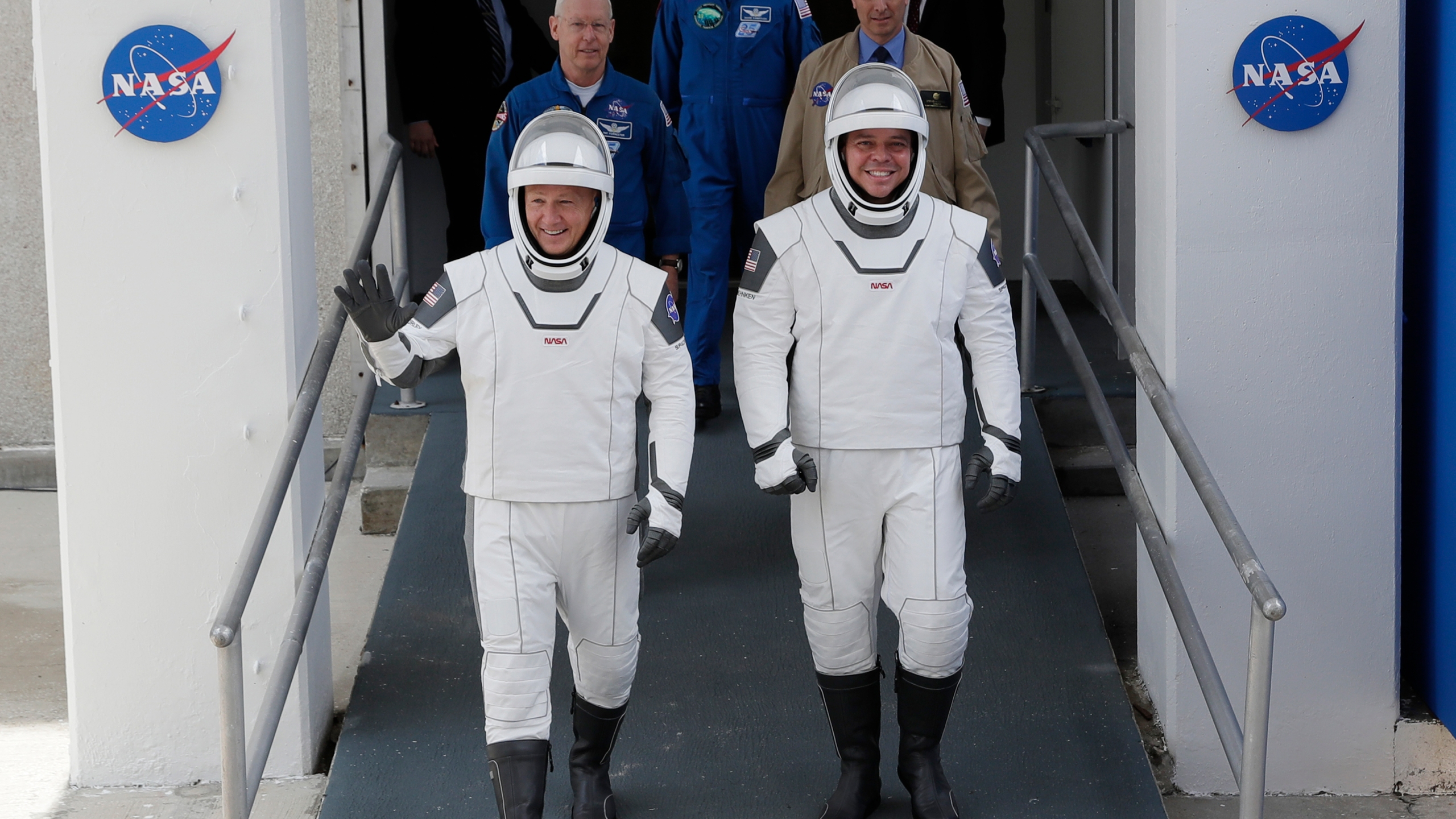 NASA astronauts Douglas Hurley, left, and Robert Behnken wave as they walk out of the Neil A. Armstrong Operations and Checkout Building on their way to Pad 39-A, at the Kennedy Space Center in Cape Canaveral, Fla., Wednesday, May 27, 2020. The two astronauts will fly on a SpaceX test flight to the International Space Station. For the first time in nearly a decade, astronauts will blast into orbit aboard an American rocket from American soil, a first for a private company. (AP Photo/John Raoux)