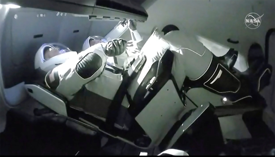 In this image taken from NASA TV video, the SpaceX Dragon crew capsule, with NASA astronauts Doug Hurley, left, and Robert Behnken aboard docks with the International Space Station Sunday, May 31, 2020. It was the first time a privately built and owned spacecraft carried astronauts to the orbiting lab in its nearly 20 years. (NASA TV via AP)