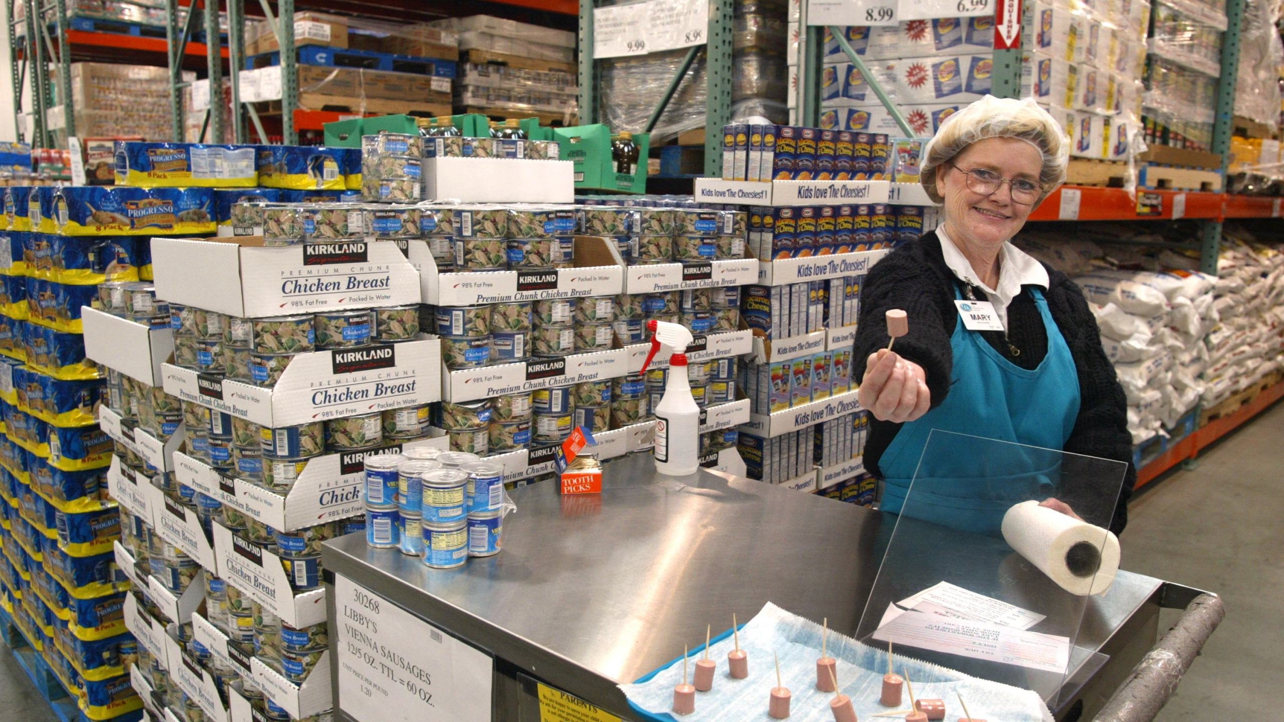 402065 04: Mary LaRocca offers a sample of Libby's Vienna Sausage in a Costco Wholesale store March 8, 2002 in Niles, IL. Warehouse retailer Costco Wholesale Corp. has reported higher quarterly profits as the promise of bulk goods at bargain prices resonated with consumers in the U.S. recession. Warehouse retailers charge customers an annual membership fee, typically $35 to $45, to shop at clubs that offer deep discounts on bulk quantities of items like food and household cleaners. (Photo by Tim Boyle/Getty Images)