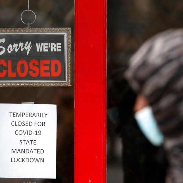 A pedestrian walks by The Framing Gallery, closed due to the COVID-19 pandemic, in Grosse Pointe, Michigan. (AP Photo/Paul Sancya)
