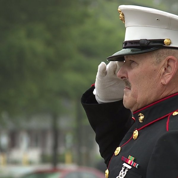 U.S. Marine veteran stands at attention along Wendover Avenue on Memorial Day to honor combat veterans