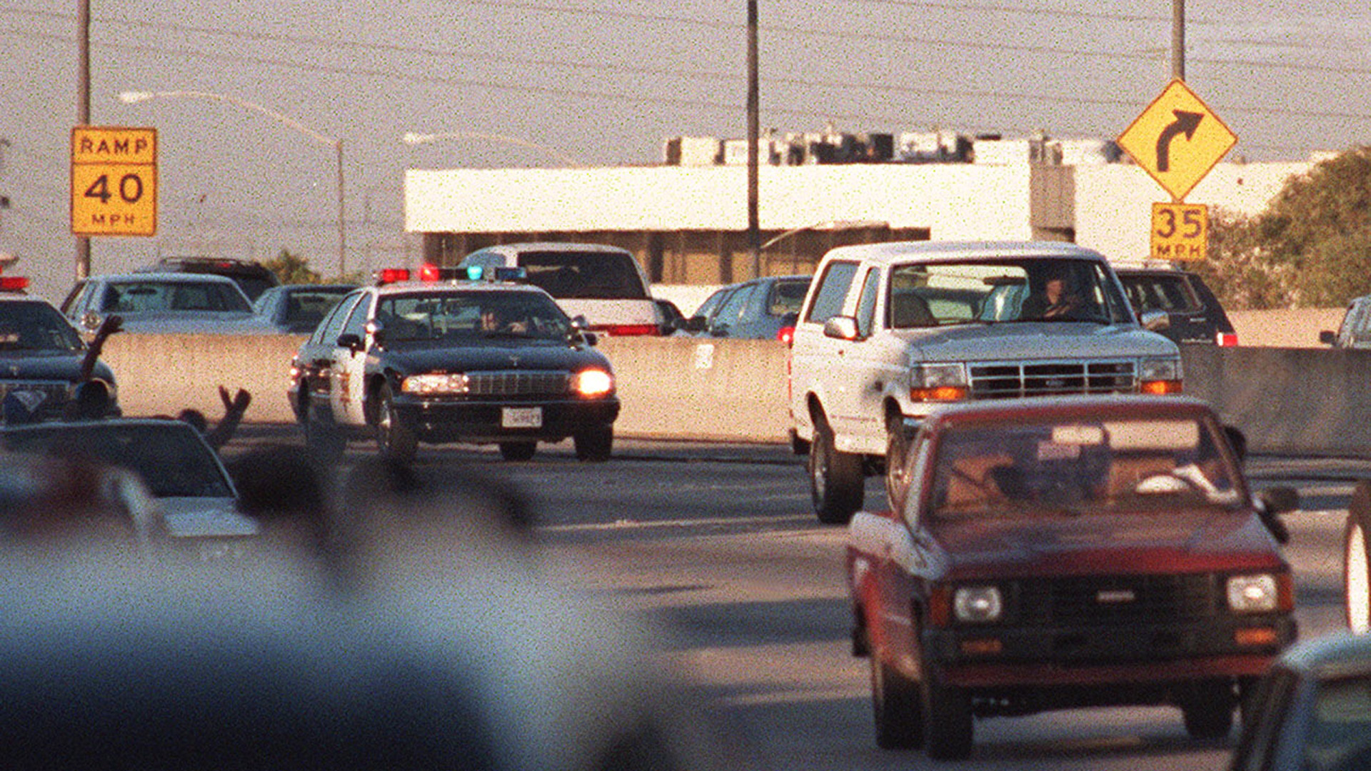 Motorists wave as police cars pursue the Ford Bronco (white, R) driven by Al Cowlings, carrying fugitive murder suspect O.J. Simpson, on a 90-minute slow-speed car chase June 17, 1994, on the 405 freeway in Los Angeles, California. Simpson's friend Cowlings eventually drove Simpson home, with Simpson ducked under the back passenger seat, to Brentwood where he surrendered after a stand-off with police. (Credit: MIKE NELSON/AFP via Getty Images)